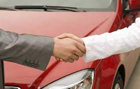 Two men shaking hands with red used car in background